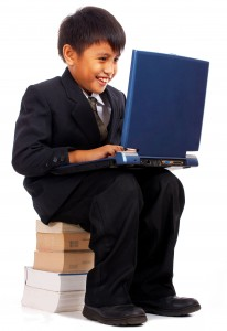 Boy With His Computer Sitting On A Pile Of Books